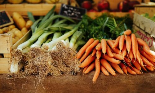 Fresh leeks and carrots are examples of produce at a farmers market